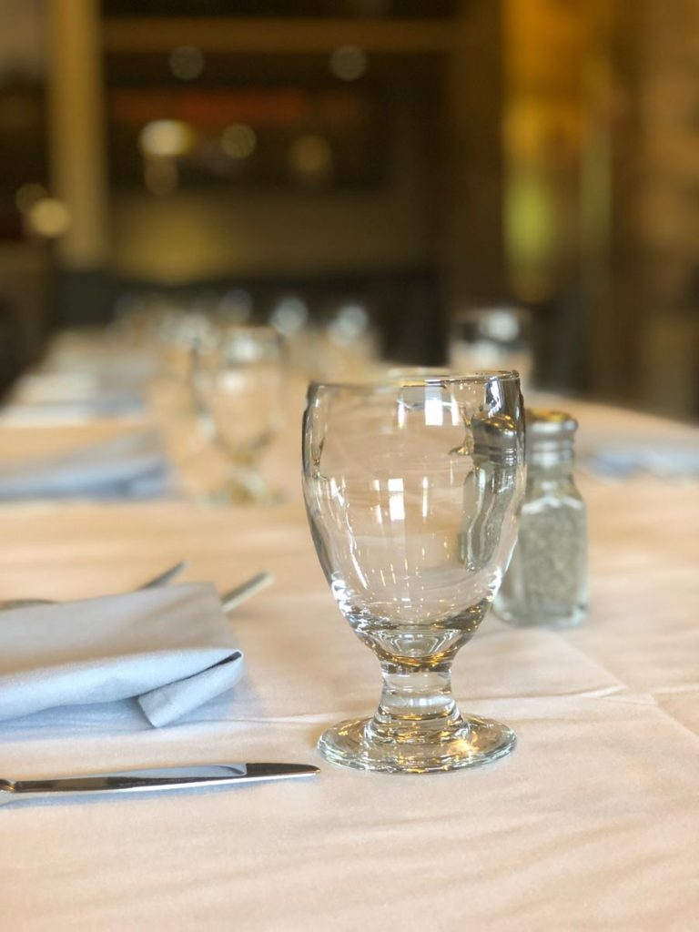 close up of place settings with dishes, utensils, and glasses