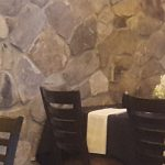 Interior of The Langton's private dining room at Matt the Miller's Carmel with place settings and flowers on tables. The table is next to a stone wall.