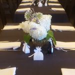 Place settings on private dining tables and centerpieces of flowers with party favors.
