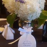 Party favors set out on private dining tables and centerpieces of flowers and salt and pepper shakers