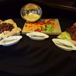 Selection of appetizers, vegetable tray, fruit tray, and cheese tray.