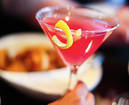 Pink cocktail drink with a lemon peel garnish, Bavarian Pretzel bites in the background
