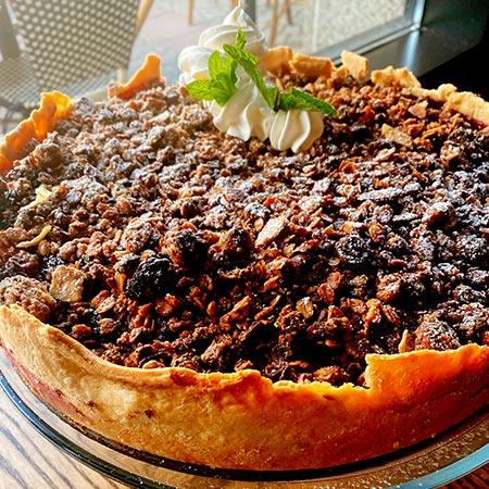 Deep dish blackberry pie with Chantilly cream garnish on serving plate.