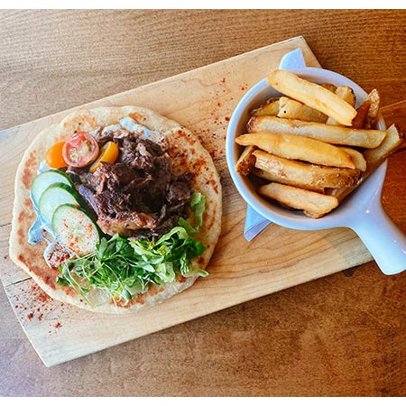 Dressed pita sandwich with prime rib meat and side of thick cut French fries.