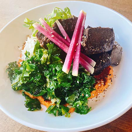 Plated dish of greens, steak tips, rice and hummus.