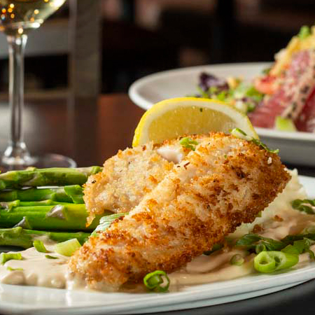 Close-up of panko-crusted walleye plated on mashed potatoes with asparagus