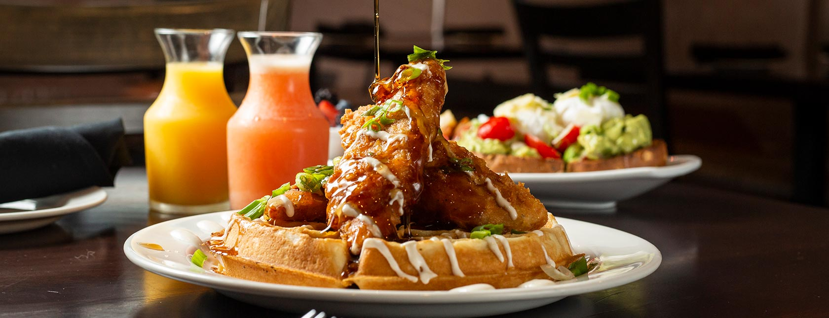 Syrup pouring over chicken and waffles with juices in background.