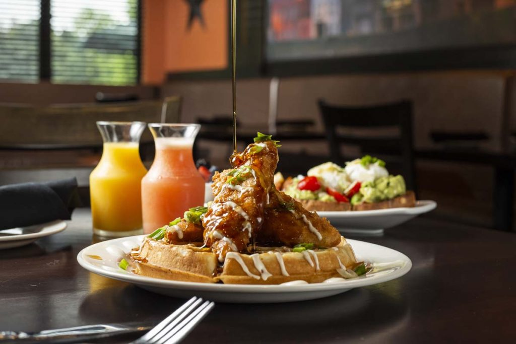 Syrup drizzling onto fried chicken-topped waffle with mini carafes of orange and pink grapefruit juice in background