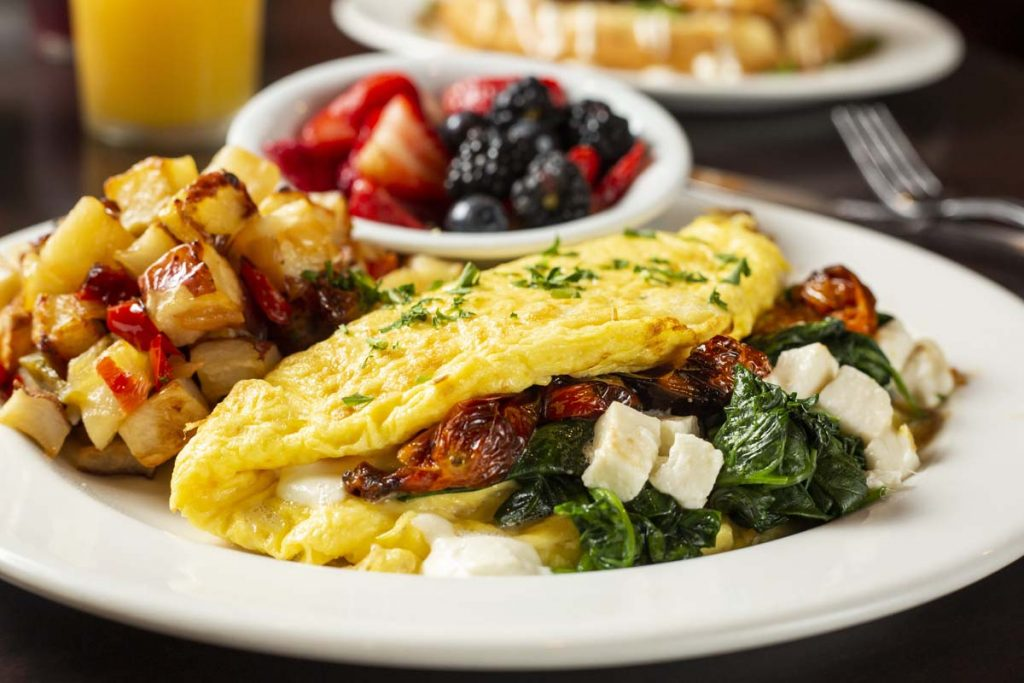 Plated omelet stuffed with mushrooms, spinach and feta cheese, sides of skillet potatoes and small bowl of fresh fruit