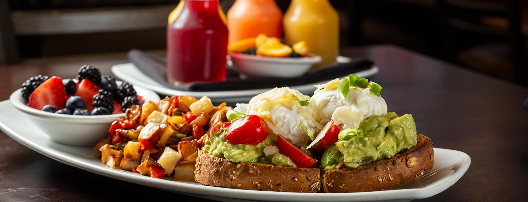 Avocado toast with potatoes and multiple juices in background