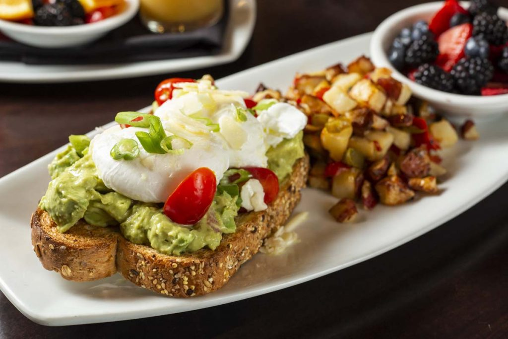 Plated avocado on toast topped with poached eggs with side of skillet potatoes