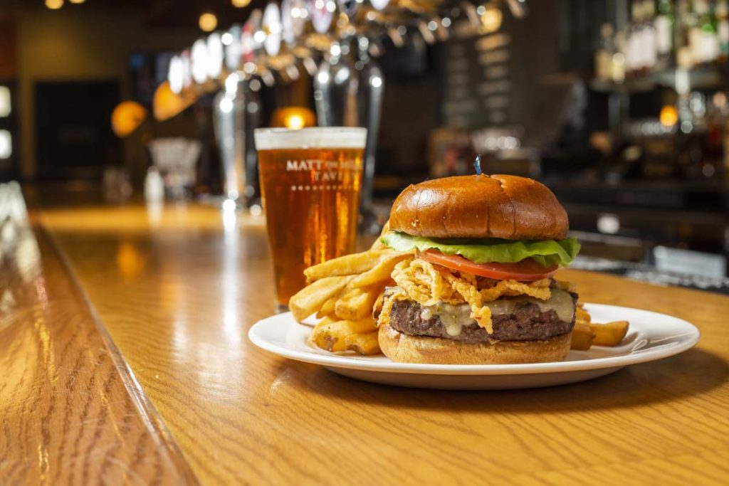 Plated burger and fries with glass of draft beer sitting on oak bar.