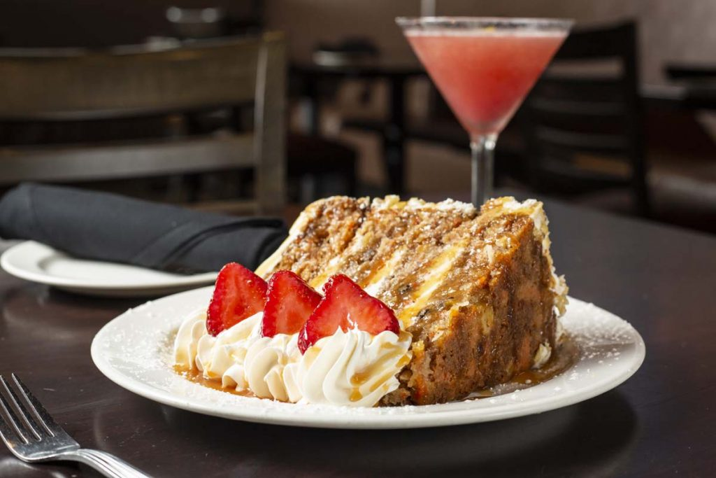 Slice of carrot cake on its side with whipped cream and strawberry garnish and pink martini cocktail in background