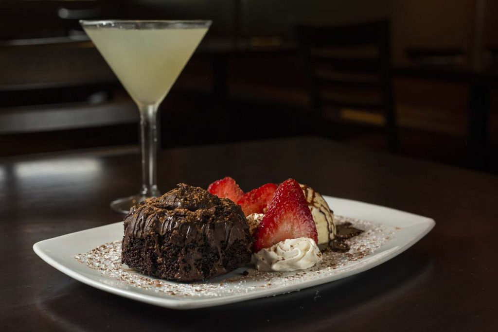 Chocolate lava cake garnished with ice cream and strawberries with lemon martini cocktail in background