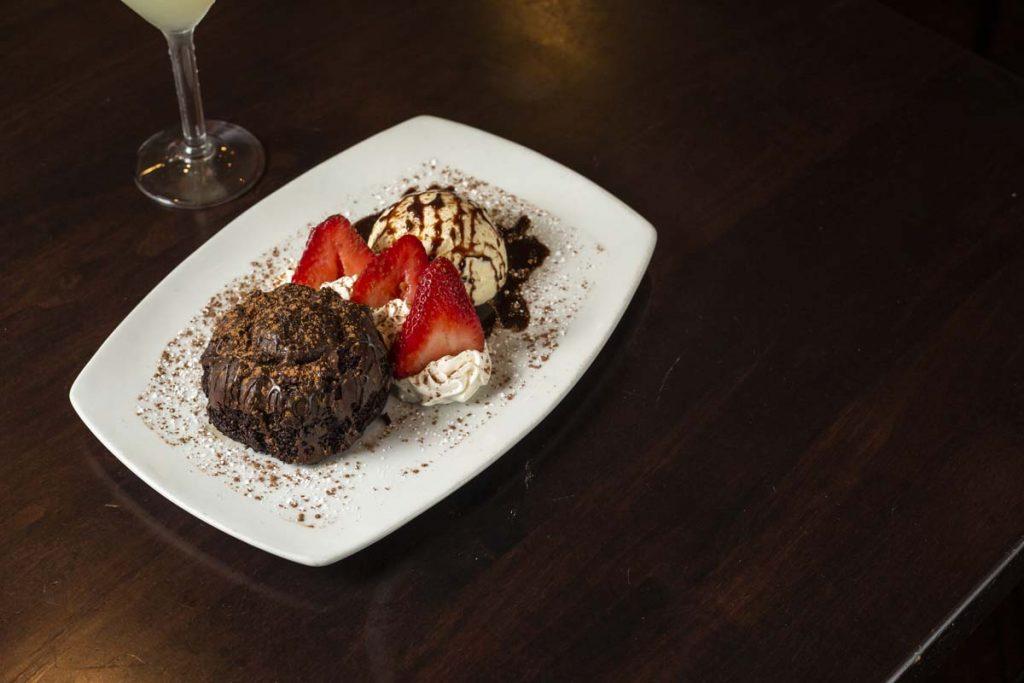 Chocolate lava cake with ice cream and strawberry garnish
