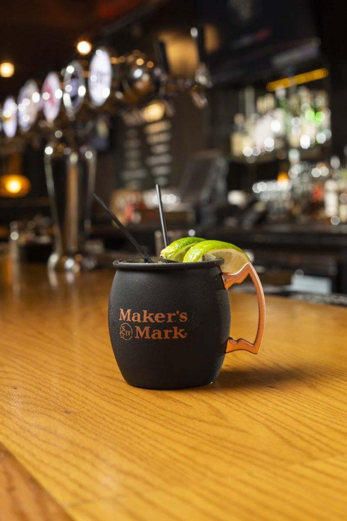 Frosty mule beverage in black Matt the Miller's mule mug with copper handle sitting on oak bar