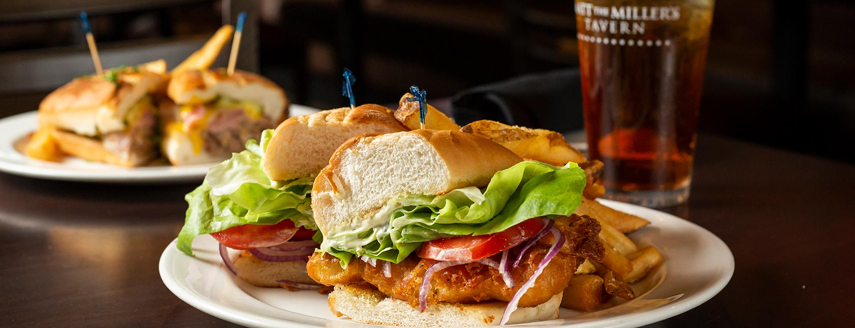 Fish Sandwich cut in half with lettuce, tomato, mayo dressing, iced tea in background