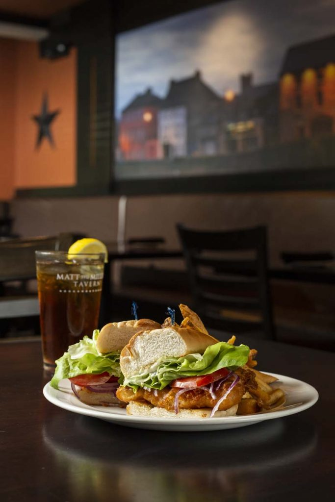 Fried fish sandwich garnished with lettuce, tomato and plated with French fries with glass of iced tea and lemon in background.
