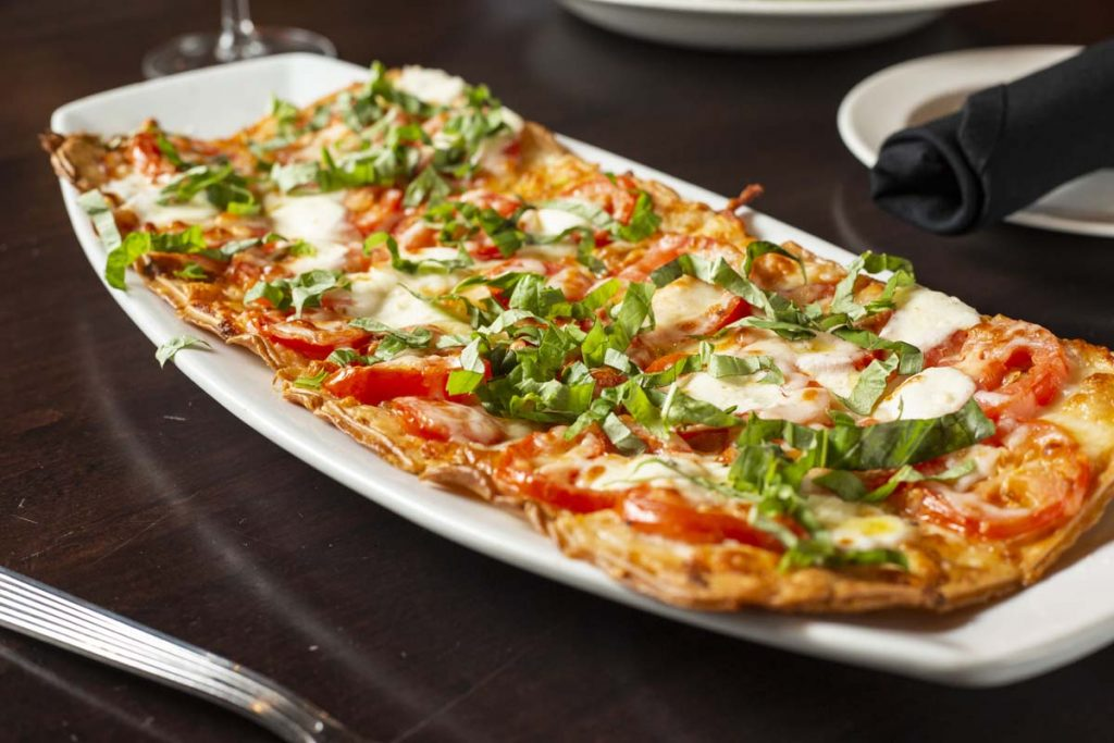 Close-up of Margherita flatbread garnished with torn basil.