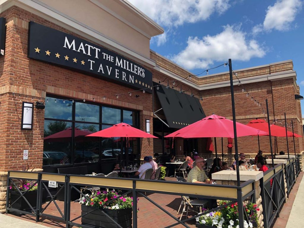Outdoor patio with red umbrellas in front of Matt the Miller's Tavern Gemini Place location.
