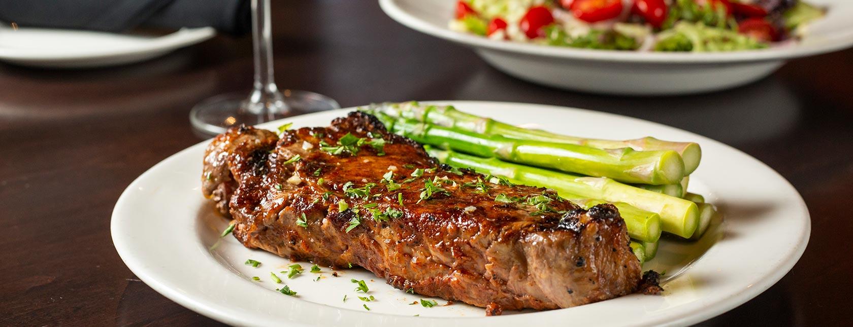 New York Strip Steak with asparagus, salad in background