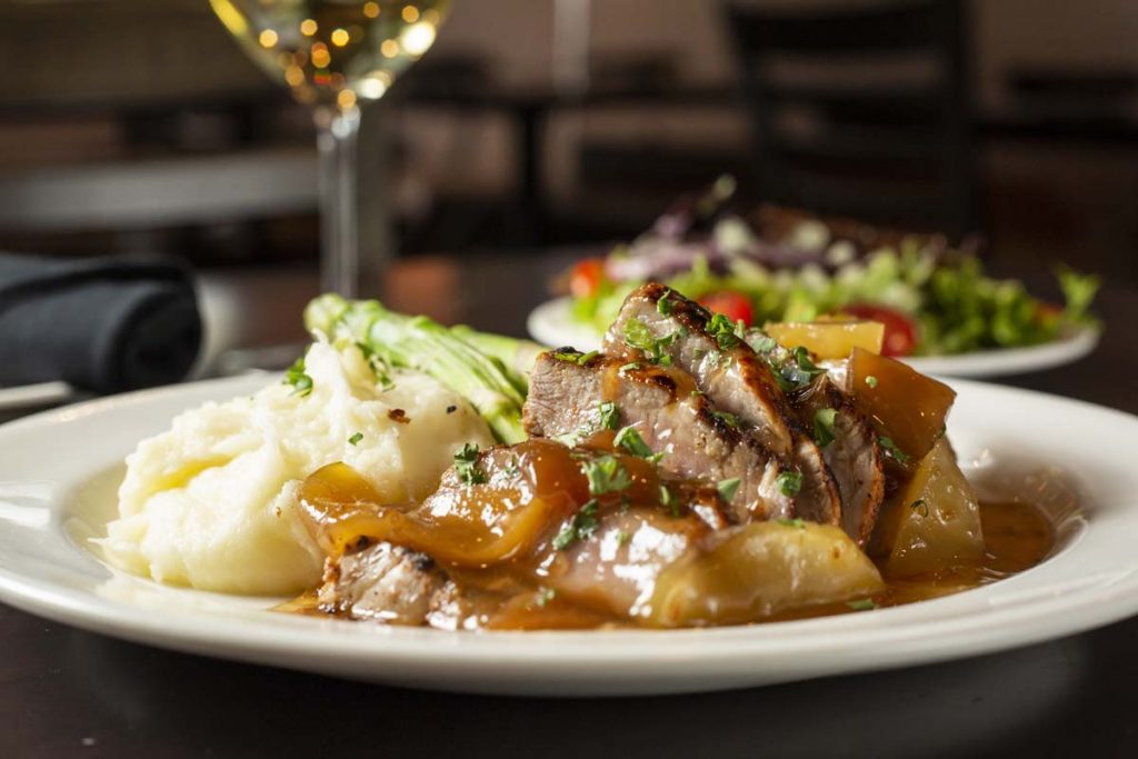 Sliced roasted pork plated with apple gravy, mashed potatoes and asparagus with glass of white wine
