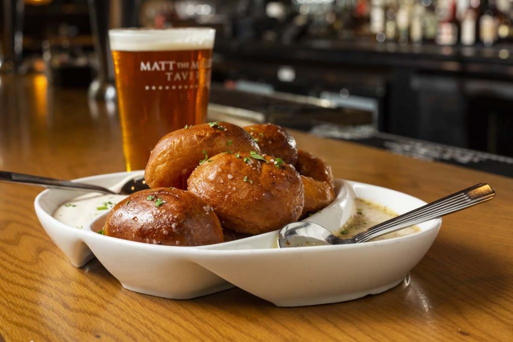 Matt the Miller's Pretzel Bites with two dipping sauces and glass of draft beer sitting on oak bar