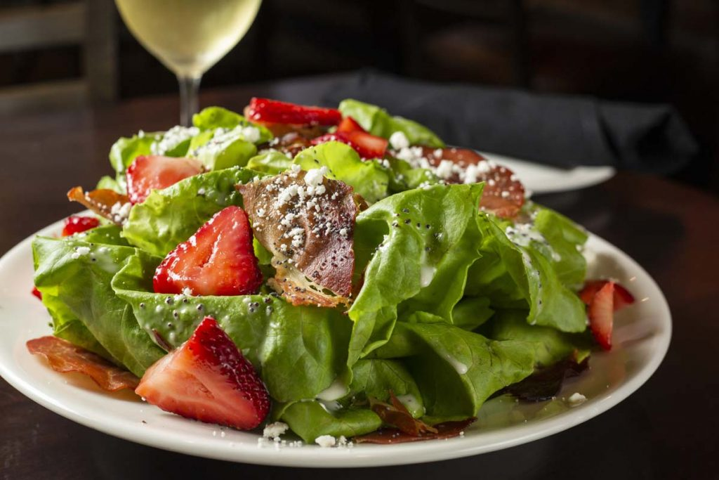 Close-up of Strawberry salad on Bibb lettuce with glass of white wine in background