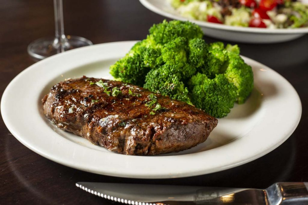 Sirloin steak plated with bright green broccoli and salad in background
