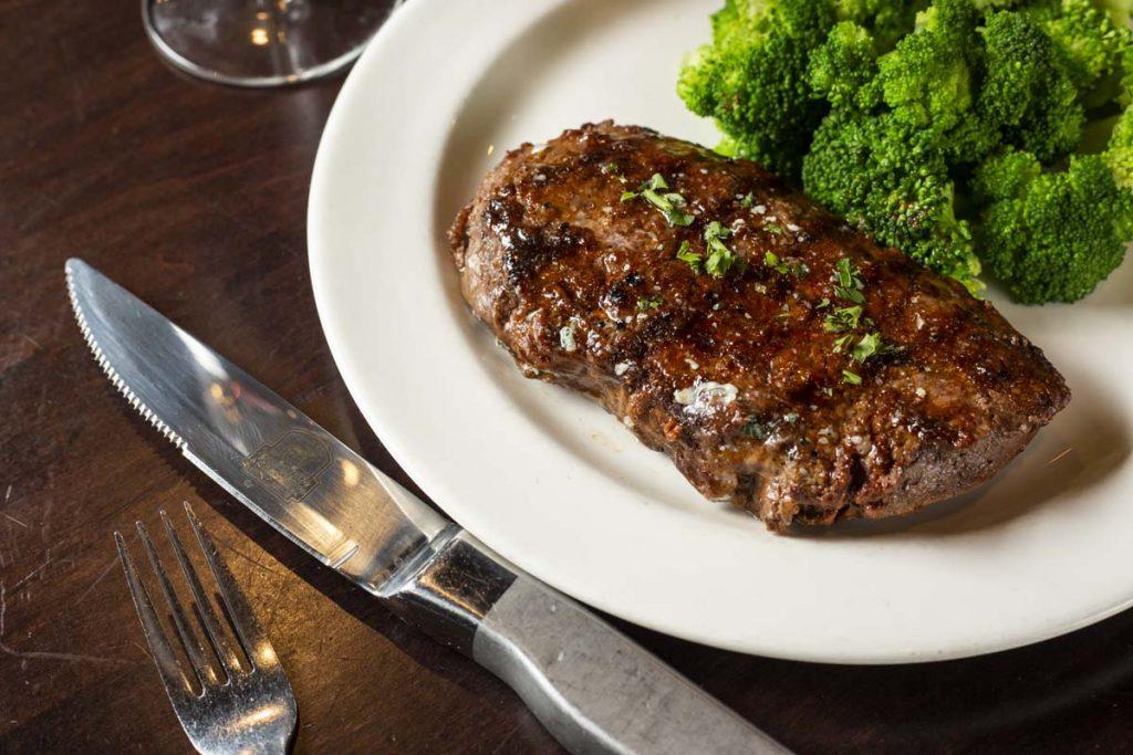 Sirloin steak plated with bright green broccoli