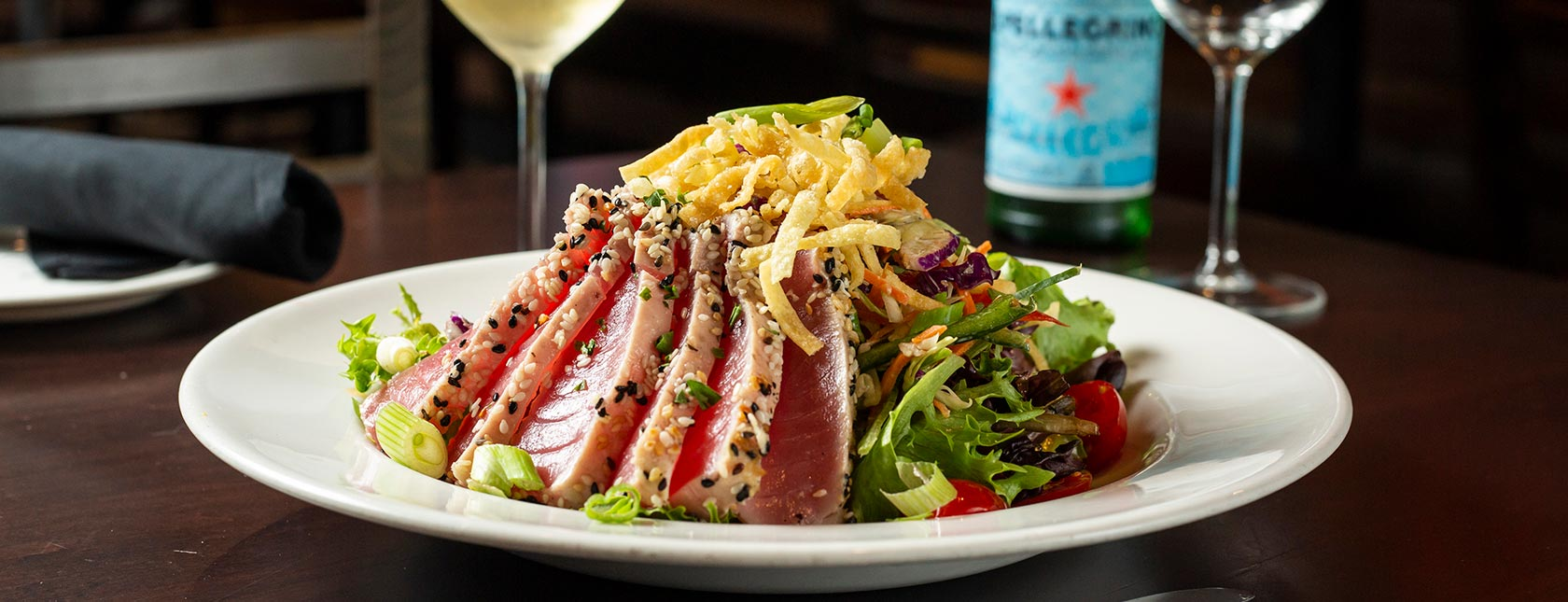 Seared tuna sliced and arranged on salad greens with beverages in background