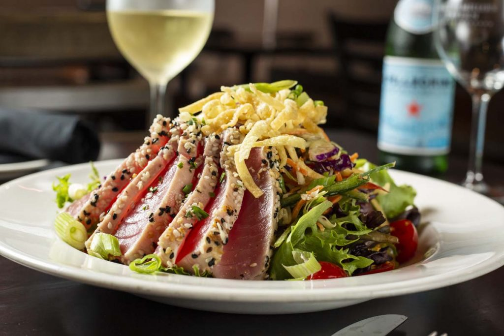 Seared rare Ahi tuna, sliced and arranged on bed of greens with glass of white wine in background