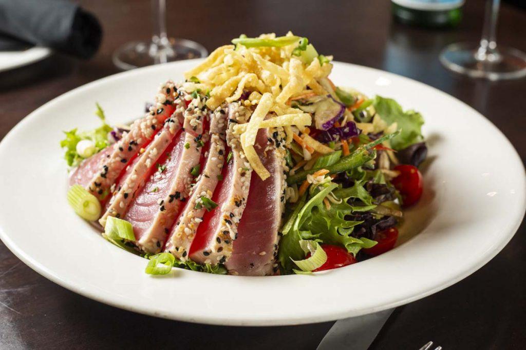 Seared rare Ahi tuna, sliced and arranged on bed of greens