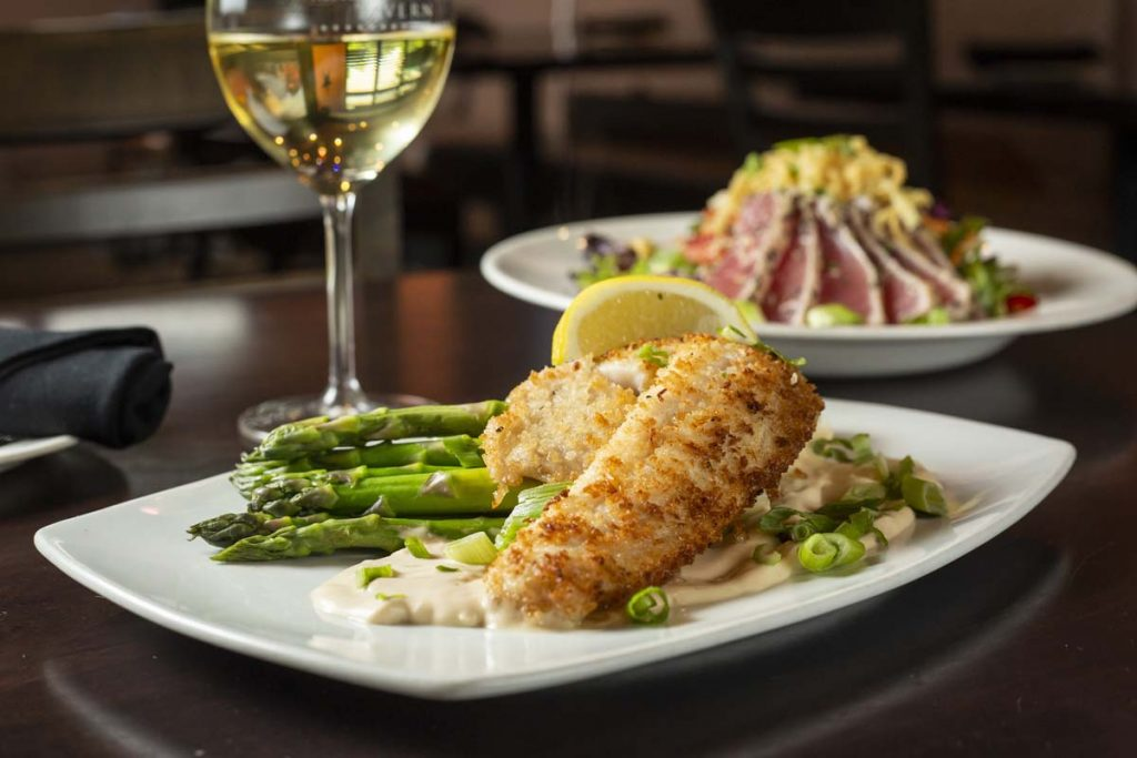 Panko-crusted walleye plated with asparagus and lemon slice with glass of white wine in background