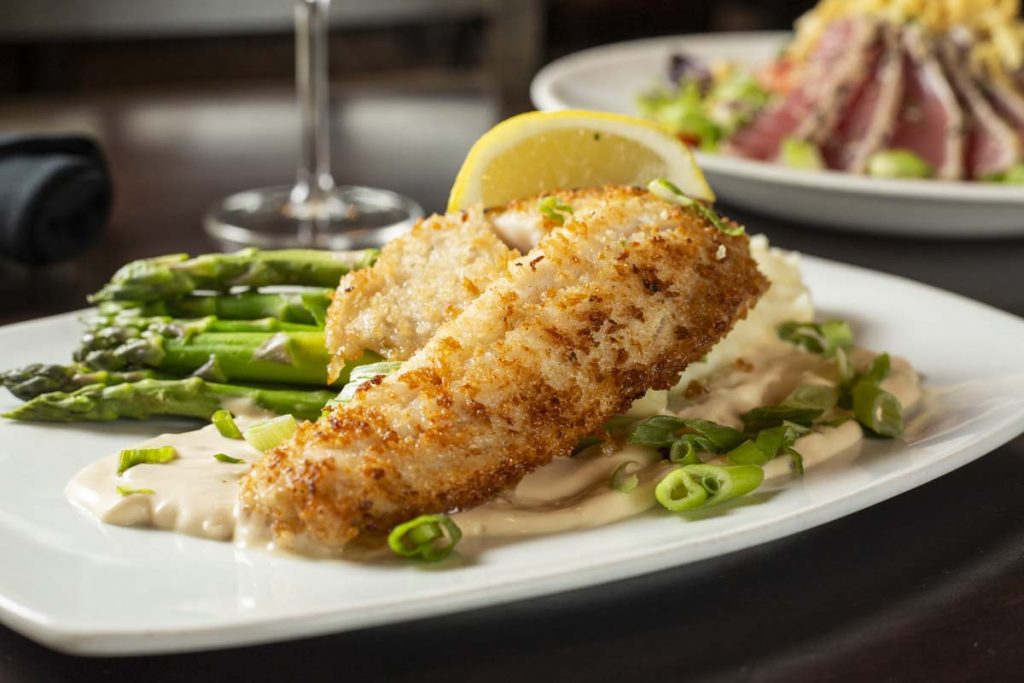 Panko-crusted walleye plated with asparagus and lemon slice