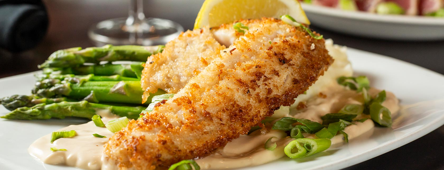 Panko-crusted, pan-fried walleye fish plated with asparagus