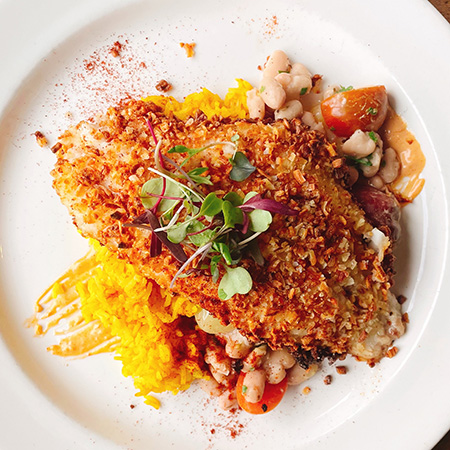 Plated potato-crusted catfish on golden rice