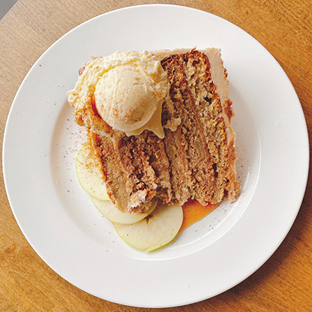 Slice of layer cake on its side with apple butter buttercream icing and scoop of house brown sugar ice cream