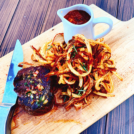 Grilled steak on wooden butcher block serving tray with French fries and cup of dipping sauce